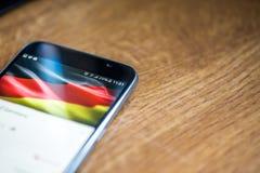 Smartphone auf hölzernem Hintergrund mit Zeichen des Netzes 5G 25-Prozent-Gebühr und deutsche Flagge auf dem Schirm Stockbilder