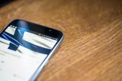 Smartphone auf hölzernem Hintergrund mit Zeichen des Netzes 5G 25-Prozent-Gebühr und Finnland-Flagge auf dem Schirm Lizenzfreie Stockbilder