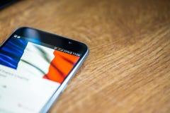 Smartphone auf hölzernem Hintergrund mit Zeichen des Netzes 5G 25-Prozent-Gebühr und Frankreich-Flagge auf dem Schirm Lizenzfreie Stockfotos