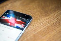 Smartphone auf hölzernem Hintergrund mit Zeichen des Netzes 5G 25-Prozent-Gebühr und Großbritannien-Flagge auf dem Schirm Lizenzfreie Stockfotos