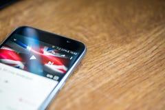 Smartphone auf hölzernem Hintergrund mit Zeichen des Netzes 5G 25-Prozent-Gebühr und Großbritannien-Flagge auf dem Schirm Stockfotografie