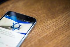 Smartphone auf hölzernem Hintergrund mit Zeichen des Netzes 5G 25-Prozent-Gebühr und Israel-Flagge auf dem Schirm Stockfotografie
