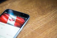 Smartphone auf hölzernem Hintergrund mit Zeichen des Netzes 5G 25-Prozent-Gebühr und Kanada-Flagge auf dem Schirm Stockfotos