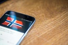 Smartphone auf hölzernem Hintergrund mit Zeichen des Netzes 5G 25-Prozent-Gebühr und Norwegen-Flagge auf dem Schirm Lizenzfreie Stockfotografie