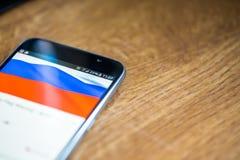 Smartphone auf hölzernem Hintergrund mit Zeichen des Netzes 5G 25-Prozent-Gebühr und Russland-Flagge auf dem Schirm Stockfotos