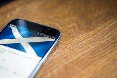 Smartphone auf hölzernem Hintergrund mit Zeichen des Netzes 5G 25-Prozent-Gebühr und Schottland-Flagge auf dem Schirm Lizenzfreie Stockfotografie