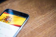 Smartphone auf hölzernem Hintergrund mit Zeichen des Netzes 5G 25-Prozent-Gebühr und Spanien-Flagge auf dem Schirm Lizenzfreie Stockfotos