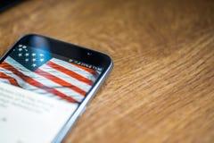 Smartphone auf hölzernem Hintergrund mit Zeichen des Netzes 5G 25-Prozent-Gebühr und USA-Flagge auf dem Schirm Stockfoto