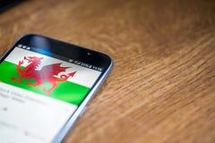 Smartphone auf hölzernem Hintergrund mit Zeichen des Netzes 5G 25-Prozent-Gebühr und Wales-Flagge auf dem Schirm Lizenzfreies Stockfoto