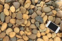 Smartphone auf Steinboden lizenzfreie stockfotos
