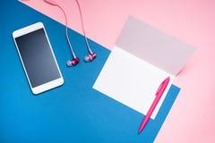 Smartphone, auriculares y hoja de papel blanca en blanco foto de archivo libre de regalías