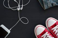 Smartphone avec des écouteurs et des espadrilles rouges sur le su en bois noir Photos libres de droits