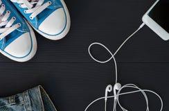 Smartphone avec des écouteurs et des espadrilles sur un surfac en bois noir Image libre de droits
