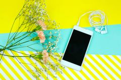 smartphone avec des écouteurs et des fleurs sur un bleu vibrant et un fond jaune dépouillé image stock