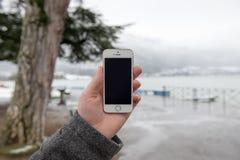 Smartphone avec l'écran d'isolement dans des mains masculines Photo stock