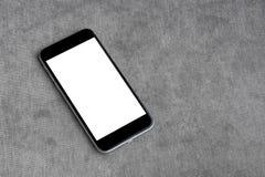 Smartphone avec l'écran et le copie-espace blancs vides sur le fond moderne de sofa Photo libre de droits