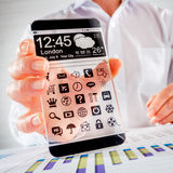Smartphone avec l'écran transparent dans des mains humaines Photographie stock