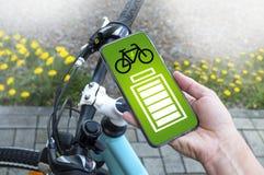 Smartphone avec l'indicateur de niveau de batterie d'appli avec le vélo d'e photographie stock libre de droits