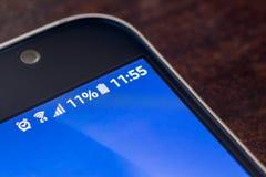 Smartphone avec la charge de batterie d'onze pour cent sur l'écran Photo stock