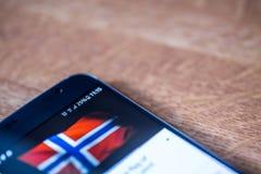 Smartphone avec la charge de 25 pour cent et le drapeau de la Norvège Photographie stock libre de droits