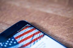 Smartphone avec la charge de 25 pour cent et le drapeau des Etats-Unis Image libre de droits