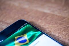Smartphone avec la charge de 25 pour cent et le drapeau du Brésil Photos stock