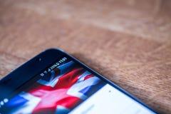 Smartphone avec la charge de 25 pour cent et le drapeau du R-U Photographie stock libre de droits
