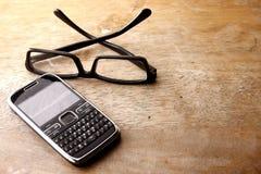 Smartphone avec le clavier numérique QWERTY et les paires de lunettes Images stock
