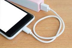 Smartphone avec le powerbank rose sur le bureau en bois Photos stock