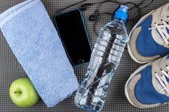 Smartphone avec les écouteurs, la bouteille, la pomme, la serviette bleue et le sneake Photographie stock libre de droits
