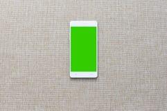 Smartphone avec sur le fond de tissu, Greenscreen Photo stock