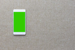 Smartphone avec sur le fond de tissu, Greenscreen Photographie stock
