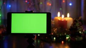 Smartphone avec un écran vert Fond de nouvelle année brouillé Une grande opportunité d'ajouter votre vidéo de salutation clips vidéos