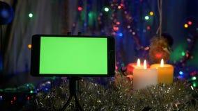 Smartphone avec un écran vert, sur un fond du ` s de nouvelle année Mouvement de l'appareil-photo autour de l'objet banque de vidéos