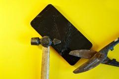 Smartphone avec un affichage cassé, des ciseaux en métal, et un marteau images libres de droits