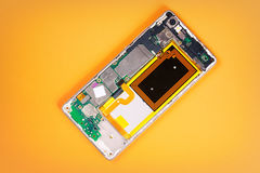 Smartphone back cover removed, showing internals on yellow background. Stock Photos