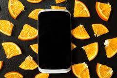 Smartphone on background of orange slices stock photos