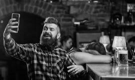 Smartphone barbu de prise de hippie d'homme Prise du concept de selfie Communication en ligne Envoyez le selfie aux r?seaux socia photo libre de droits