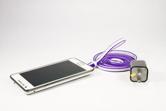 Smartphone with battery charger Stock Photos