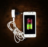 Smartphone with battery on the screen and the charging wire Royalty Free Stock Image