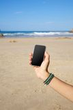 Smartphone in the beach Royalty Free Stock Photography