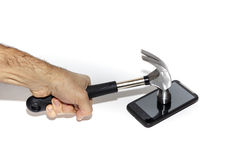 Breaking Communication. Male hand hitting smartphone with a hammer, trying to picture escaping from todays always connected world of smartphones Stock Photos