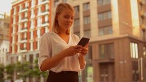 Smartphone bem sucedido do uso da mulher de negócios na rua filme