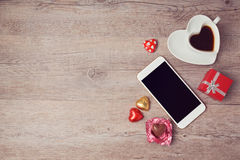 Smartphone bespot omhoog vlak legt voor de dag van Valentine met koffiekop en chocolade Mening van hierboven Royalty-vrije Stock Foto