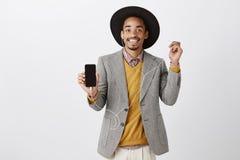 Smartphone bestämt värt köpa Stående av den tillfredsställda snygga afrikanska kunden i flott dräkt och hatt som visar royaltyfri fotografi
