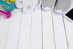 Smartphone, białe słuchawki, sportów buty, kolorów dumbbells fotografia stock