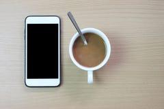 Smartphone bianco con lo schermo in bianco e la tazza di caffè macchiato neri sopra immagini stock libere da diritti