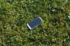 Smartphone bianco perso che si trova nell'erba Immagini Stock