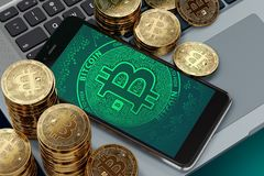 Smartphone with Bitcoin symbol on-screen laying on computer keyboard around Bitcoin piles Stock Image