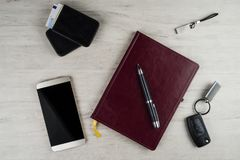 Smartphone, biurko ochraniacz, zapłonowy klucz, pióro i inni mężczyzna ` s akcesoria na powierzchni z teksturą bielący dąb, fotografia royalty free